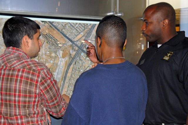 Staff Sgt. Rodney Smith, one of more than 20 Soldiers who man the Army Experience Center in Philadelphia, uses the Global Base Locator to teach visitors about the many Army installations throughout the world. The AEC opened its doors to the public at the Franklin Mills Mall Friday.