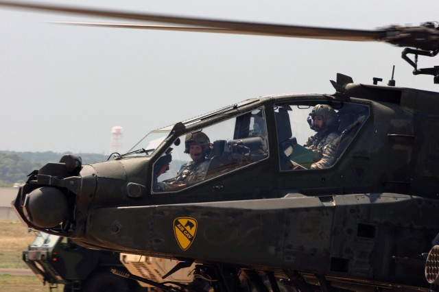 """Chief Warrant Officer 4 James """"Jimbo"""" Snyder (back seat), an AH-64D Apache attack helicopter pilot for 1st """"Attack"""" Battalion, 227th Aviation Regiment, 1st Air Cavalry Brigade, 1st Cavalry Division, taxis his aircraft back to his parking spot while Chief Warrant Officer 2 Robert Seybold, the production control officer for 1st Attack, smiles like he just won the lottery. And he basically did. He and a select few other Soldiers were given the rare opportunity to ride in the front seat of an Apache - a place exclusively reserved for attack pilots. The troopers took 30-minute flights, taking off from Robert Gray Army Air Field, Fort Hood, Texas, Aug. 26."""