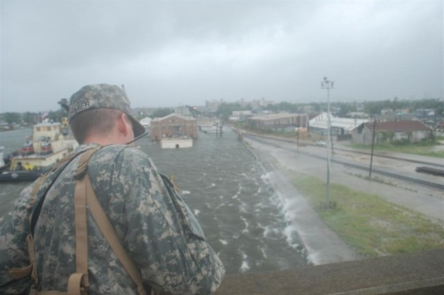 A Louisiana National Guardsman observes from the Claiborne Ave. bridge in New Orleans as water from the Industrial Canal overtops the levees and pours into the city Monday