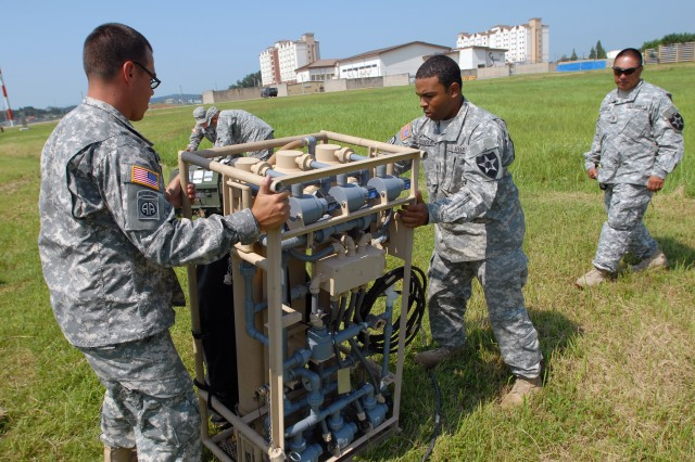 Sgt. Matthew Frey (left) and Warren Robinson (center) of Alpha Company, 602nd Aviation Support Battalion move a filtration unit during training on the Light Water Purification System. Fuel and Water Platoon Sergeant Alberto Aguirre (far right) looks on.