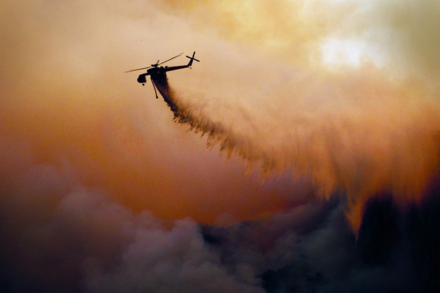 """An S-64 Aircrane firefighting helicopter drops 2,000 gallons of water over the """"Indians"""" wildfire outside Fort Hunter Liggett, Calif., June 19. The wildfire, which has been burning since, June 8, is believed to have been started by an unattended campfire."""