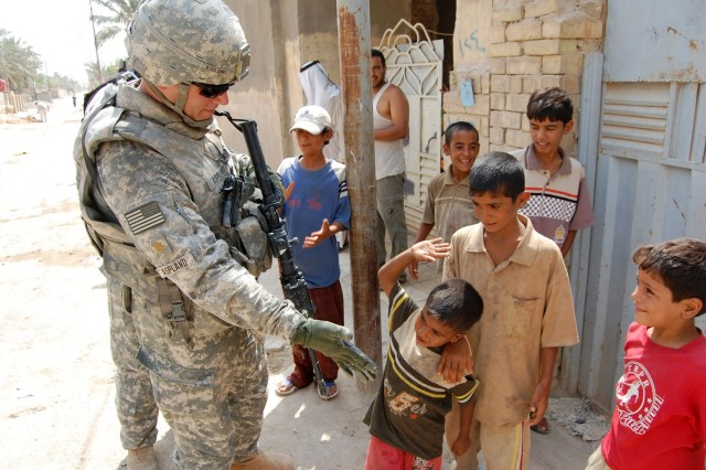 Maj. Patrick Aspland, a Fort Ann, N.Y., native, gets a 'five' from a young child while leaving the Boob al-Sham community, northeast of Baghdad, Aug. 25. Aspland is the executive officer for the 1st Battalion, 27th Infantry Regiment, 2nd Stryker Brigade Combat Team, 25th Infantry Division, Multi-National Division-Baghdad.