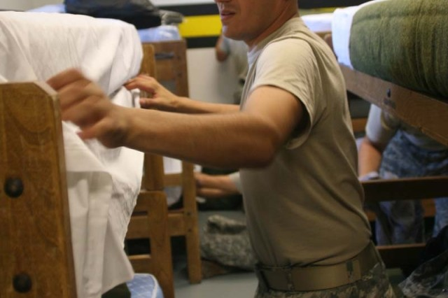 Staff Sergeant Christopher Acevedo works on his bunk as he and 19 others settle in on their first day of Assessment and Selection with the U.S. Army Parachute Team.