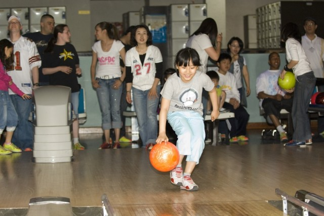 A Korean elementary school student bowls at Yongsan Lanes during a Good Neighbor Program event. The bowling center opens its lanes several times a year for special events such as these, which helped earn the center a top Army award.