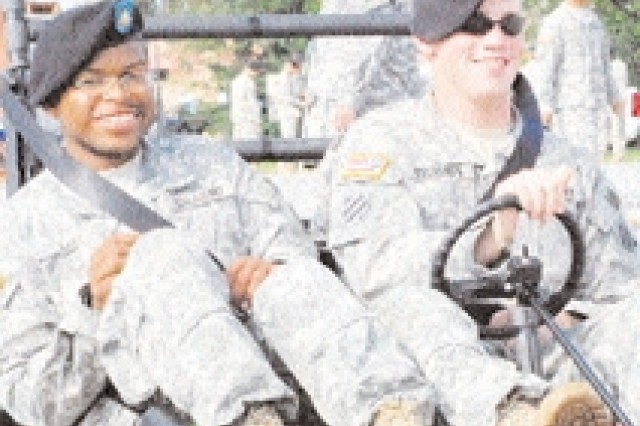 Pfc. Brandon East, 3rd BSB, and Pvt. Dustin Bohannon, HHC, 3/39 Armor, try their hand at the Simulated Impaired Driving Experience, an electronically controlled go-cart used to simulate the effects of drunk driving at the Installation Safety Day, Aug. 26.
