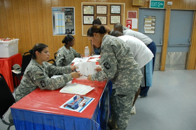 Captain Mary Smith, S1, Brigade Troops Battalion, 4th Sustainment Brigade (seated, left) and Cpt. Latoya James, S1, 4th Sustainment Brigade (seated, right) take their Voting Assistance Officers duties to the troops during an Armed Forces Voter Week event at a Camp Arifjan, Kuwait dining facility, Sept. 2, 2008. According to Smith, more than 100 Soldiers and civilians took advantage of their absentee voting advice and assistance.