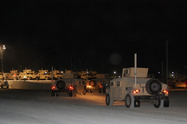 After being prepared for delivery by 3rd Battalion, 401st Army Field Support Brigade, up-armored High Mobility Multi-purpose Wheeled Vehicles, destined for issue to warfighters of 4th Infantry Division's 2nd (Warhorse) Brigade Combat Team, are loaded for transport at the Army Materiel Command's logistics hub at Camp Arifjan, Kuwait, Sept. 4, 2008.