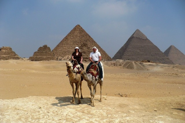 With the Giza Pyramid Complex at their backs, Personnel specialist Rena Barlow (left) and budget analyst Brandon Cooper, 401st Army Field Support Brigade, sit astride dromedary camels, Sept. 2, 2008.  Barlow and Cooper, Department of the Army civilian volunteers deployed to Southwest Asia from McAlester Army Ammunition Plant, McAlester, Okla., and Rock Island Arsenal, Illinois, respectively, traveled to Egypt from Camp Arifjan, Kuwait.