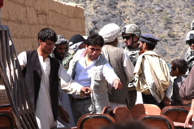 A local contractor from an Afghan construction and supply company counts desks with villagers in the Kohi Sofi district of Afghanistan's Parwan province as Task Force Gladiator soldiers distribute school supplies, Aug. 26, 2008.