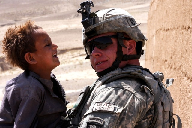 A child from the Kohi Sofi district of Afghanistan's Parwan province, laughs at Sgt. Jeremy Smith of Task Force Gladiator's Alpha Company. The task force distributed school supplies to the district's Shawo Katay, Hasanzi and Jurghati villages on Aug. 26, 2008.