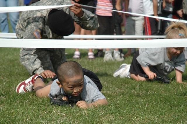 Renz Du low-crawls under an obstacle during a Youth Spur Ride for children of Soldiers assigned to the 2nd Stryker Cavalry Regiment from Vilseck, Germany.