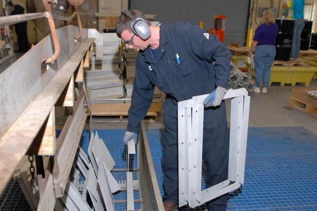 Mike Benjamin, electroplater worker, loads a basket with sandblasted aluminum parts.