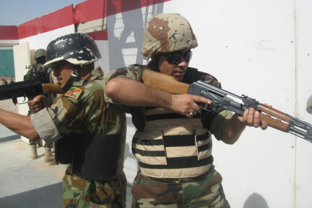 Two IA trainer candidates pull security after entering a house to detain suspected criminals during training at Camp Dhi Qar's basic training site on COB Adder. ""