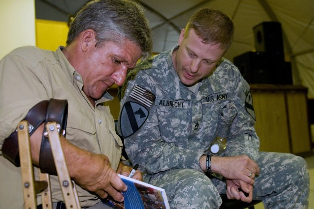 "Matt Roloff, star of The Learning Channel's show ""Little People, Big World"" signs a book for Sgt. First Class Kevin Albrecht from the Headquarters and Headquarters Company, 4th Special Troops Battalion, 4th Brigade Combat, 1st Cavalry Division at the Camp Adder Warrior Memorial Hall Sept. 6."