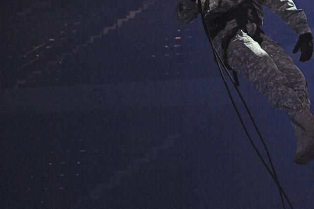 """Staff Sgt. Jared Keyworth descends to the floor of the Blue Cross Arena during """"tech-in"""" of rappeling sequences for the Military District of Washington's production of Spirit of America. The show opens at the end of the week drawing audiences that have requested tickets for the free Army show. Keyworth is with A Company, 4th Bn., 3rd U.S. Infatntry Regiment (The Old Guard)."""