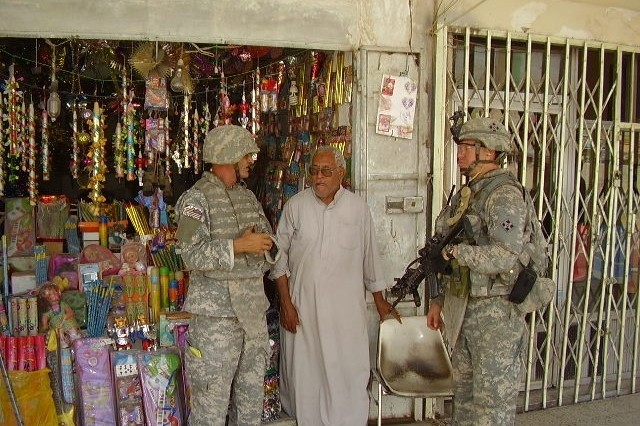 1st Lt. Matthew George, a Los Angeles native, talks with a candle shop owner in northern BaghdadAca,!a,,cs Shaab neighborhood with the help of an interpreter during a patrol, Sept. 6.