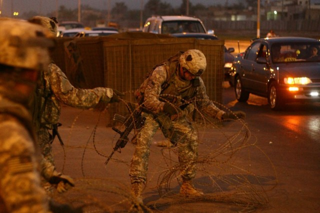 Beneath the streetlights of northwest Baghdad's Hurriya neighborhood Multi-National Division - Baghdad Soldiers with Company A, 1st Battalion, 502nd Infantry Regiment, grab hold of concertina wire. Soldiers plan to gather up as much concertina wire as they can and use safety cones in its place whenever possible in an effort to beautify Hurriya.