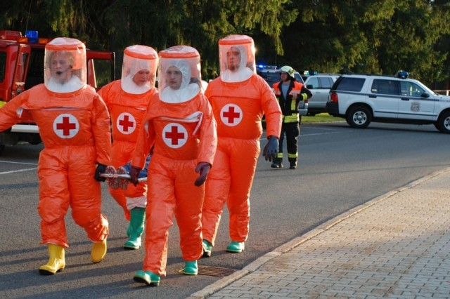"""Bavarian Red Cross stretcher bearers carry a role-player """"casualty"""" to the decontamination site during a force protection exercise held Sept. 5 at U.S. Army Garrison Garmisch, Germany."""