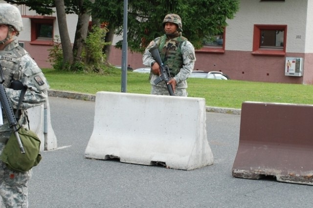 Spec. William Runyon, left, Spc. Demetrius Castle and Pfc. Michael Hackett, 18th Combat Sustainment Support Battalion,  take up a checkpoint posture outside of the U.S. Army Garrison Garmisch, Germany, headquarters building during a force protection exercise Sept. 5.