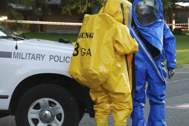 """Two Garmisch, Germany, civilian firefighters suit up to enter the """"contamination"""" zone during a force protection exercise held Sept. 5 at U.S. Army Garrison Garmisch. Garrison Military Police within the danger area also donned protective suits, while Soldiers from the 18th Combat Sustainment Support Battalion located farther from the scene wore full battle dress, body armor and masks."""