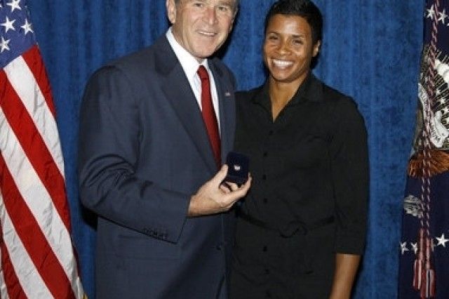 President George W. Bush stands with Keela Carr, a 35-year-old fitness and athletic trainer from Orlando, shortly after his arrival in the Florida city Aug. 20.  Carr was recognized by the U.S. Army's Freedom Team Salute Program and named its 500th Volunteer Ambassador.   photo by