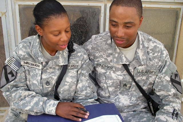 Staff Sergeants Kelvin and Michelle Windham sit and review documents outside their living area Sep 7.  The Windham's are assigned to 27th BSB, 4st BCT, 1st Cav. Div.