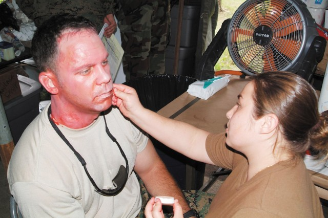 U.S. Navy HM2 Shyla Glynn, A moulage (make-up) artist applies make up to a first-year medical student to give the appearance of a flash burn. First-year students act as patients for the fourth-year students during Operation Bushmaster.