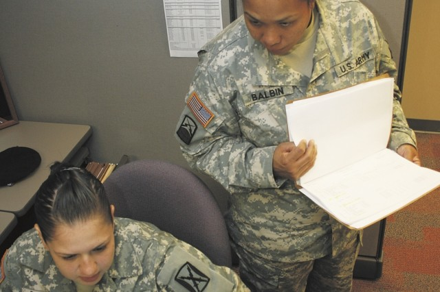 Spc. Grecia Ramos, a human resources specialist, and Master Sgt. Jerri Balbin, an information systems chief, of the 106th Signal Brigade, review enlisted personnel records Sept. 5 at the old Brooke Army Medical Center. Still in its cadre phase, only 13 Soldiers are on board at the 106th Sig. However, when at full strength in 2010, the brigade will have 90 Soldiers and 96 civilians.