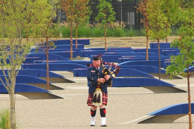 "A bagpipe player performs ""Amazing Grace"" prior to the dedication of the Pentagon Memorial Sept. 11."