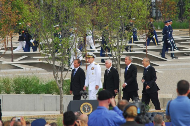 The official party marches off after dedicating the Pentagon Memorial, from left: Pentagon Memorial Fund Chairman James J. Laychak, Chairman of the Joint Chiefs Adm. Michael Mullen, Secretary of Defense Robert M. Gates, President George W. Bush, and former Secretary of Defense Donald Rumsfeld.