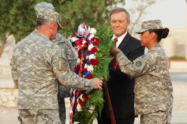 Sgt. Bernina Blackwater, chaplain assistant, U.S. Army Area Support Group - Qatar, assists U.S. Ambassador to the State of Qatar, Joseph E. LeBaron, with placing a memorial wreath during the Camp As Sayliyah, Qatar, Patriot Day Ceremony, Sept. 11, 2008. Also helping place the wreath is Col. David G. Cotter, Commander, ASG-Qatar, and Command Sgt. Maj. Michael D. Howard, ASG-Qatar Command Sergeant Major. (U.S. Army photo by Jim Hinnant)
