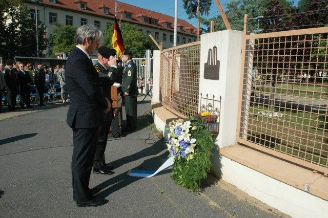DARMSTADT, Germany - Lt. Col. Dan McFarland, commander of the 2nd Military Intelligence Battalion, salutes and Johann Partsch, Darmstadt city Stadtrat (city council member) bows his head in respect after laying a wreath at the plaque remembering the Sept. 11, 2001, attacks in New York, Washington and Pennsylvania. The ceremony was the last joint German-American observance of 9/11 and of the World War II 1944 bombing raid that virtually destroyed this city's center, killing 12,000 people. All operations of U.S. Army Garrison Darmstadt officially cease Sept. 30, with a transition team preparing its installations for turnover to the German government. The plaque was donated by the citizens of Darmstadt.