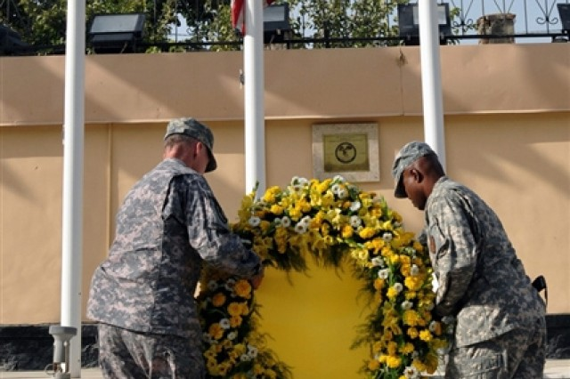 Army Maj. Gen. Robert Cone, commander of Combined Security Transition Command - Afghanistan, and Army Sgt. Maj. Gregory Valcin, acting CSTC-A command sergeant major, place a wreath below a flag flown at half-staff during a remembrance ceremony at Camp Eggers in Kabul, Afghanistan, Sept. 11, 2008