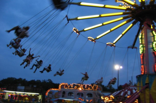 Festival goers enjoy the thrill of the giant swing as they fly out over the carnival midway during Oktoberfest 2007.