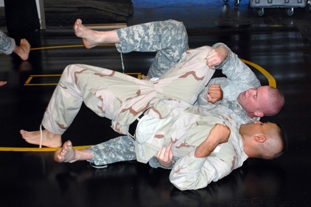 An unidentified Soldier gives SMDC/ARSTRAT Noncommissioned Officer of the Year, Staff Sgt. Christopher Barber (in ACUs) a difficult time during combatives training. Barber is training to compete in the Department of the Army Best Warrior Competition later this month.