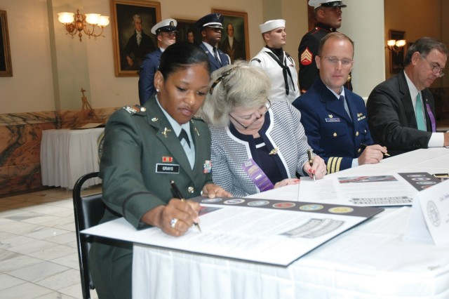 Col. Deborah B. Grays, U.S. Army Garrison commander, joins area commanders in signing the Gerogia Armed Forces Community Covenant agreement Tuesday at the State Capitol.