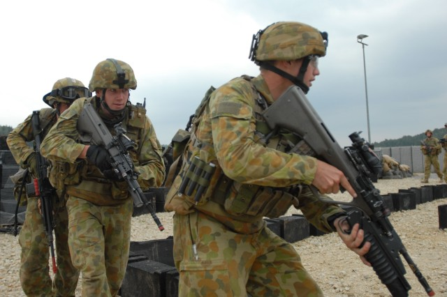"""Australian soldiers from 8 Platoon, Charlie Company, 1st Battalion, Royal Australian Regiment practice building clearing procedures before moving on to the Aca,!A""""shoothouseAca,!A? at the Joint Multinational Readiness Center in Hohenfels, Germany."""