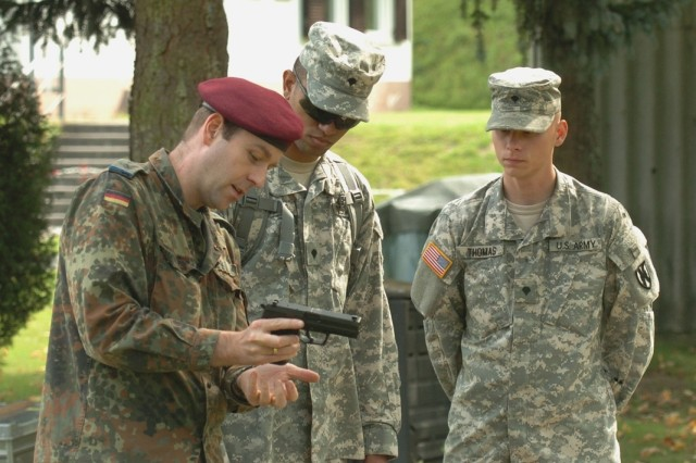 German Joint Support Command 1st Lt. Christophe Kiko trains Spc. Alexander Torres and Spc. Dorrian Thomas from 21st Theater Sustainment Command on the German P8 pistol, which they later would qualify with, receiving the opportunity to earn the Schützenschnur Badge.