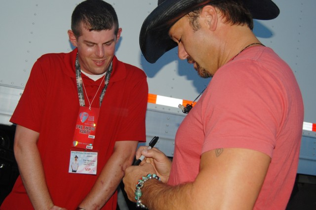 Country superstar Tim McGraw signs an autograph for Warrior in Transition Staff Sgt. Allan Annaert. McGraw met with several wounded warriors and their Families backstage before the concert to thank them for their sacrifice.