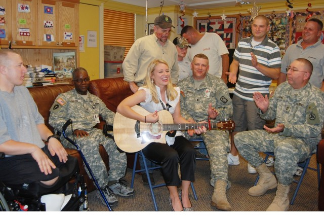 Katie Rae Davis gives a special performance for Warriors in Transition at the Warrior and Family Support Center in the Powless Guest House here. Davis later performed for about 25,000 service members and their Families at MacArthur Parade Field as the opening act for the Tim McGraw concert.