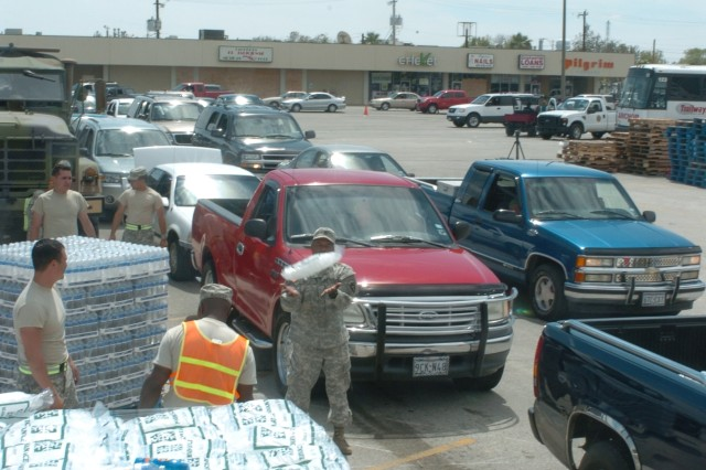 Texas National Guard Soldiers distribute ice and water at the Texas City, Texas point-of-distribution site.