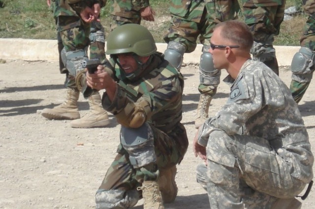 """A-""""A?A-""""A?Sgt. Adam Zimmerman, a native of Sylvania, Ohio, coaches Afghan National Arny Staff Sgt. Assadullah Abdul Saleem on proper 9mm firing techniques during a weapons familiarization class."""