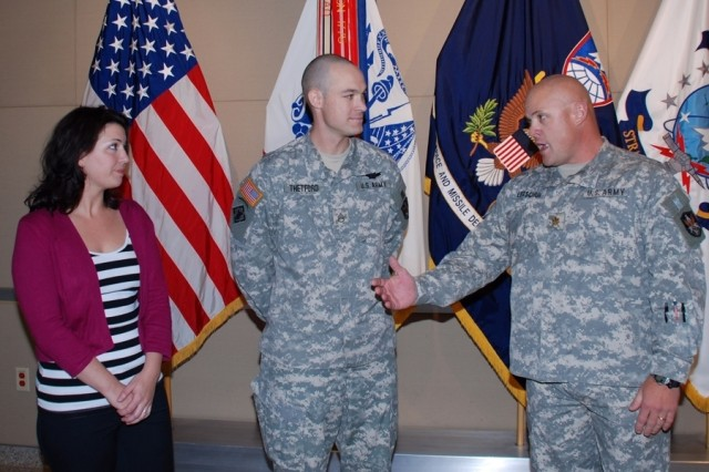 Staff Sgt. Thomas Thetford (center), member of the Army Space Support Team #5, is welcomed home by Maj. Todd Leitschuh (right), commander of the 2nd Space Company, 1st Space Battalion, during a brief ceremony Thursday morning at SMDC/ARSTRAT Operations ON Peterson Air Force Base, Colo., as Thetford's wife Barbra looks on. Thetford returned early from duty in theater to get ready to attend Warrant Officer Candidate School in the fall.