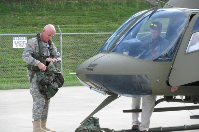 Maj. Gen. Jim Myles, AMCOM LCMC commander, adjusts his pilot gear before flying the Bell Jet Ranger from the Prototype Integration Facility to the Madison County Executive Airport in Meridianville.