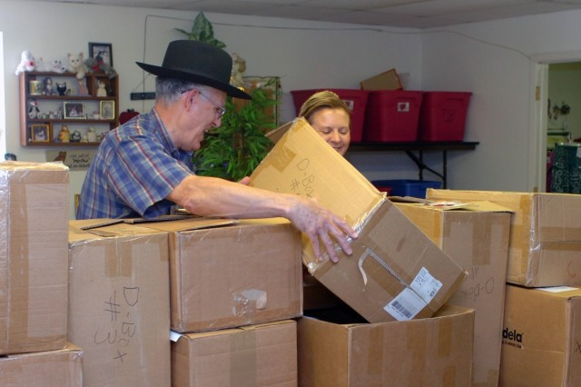 Col. (ret.) Herb Lawson, former commander, Division Support Command, 1st Cavalry Division, shares a laugh Sept. 10 at Fort Hood, Texas with Margret Bond, the Fort Hood thrift shop manager, as they stack boxes containing $32,000 in maternity items which Lawson and his wife MurAnne donated to the thrift shop.