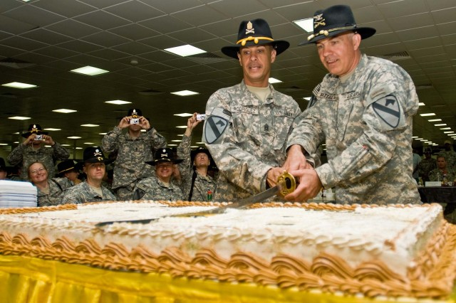 Command Sergeant Major Edwin Rodriguez and Col. Philip Battaglia use a saber to cut the birthday cake during the Long Knife Brigade's birthday party for the 1st Cavalry Division at Contingency Operating Base Adder Sept. 13.