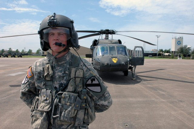 Sgt. Timothy Vasdine, a UH-60 Black Hawk crew chief for Company A, 2nd Battalion, 227th Aviation Regiment, 1st Air Cavalry Brigade, 1st Cavalry Division, stands ready for a mission to fly Gen. Victor Renuart Jr., commanding general of U.S. Northern Command, and his staff. The Lobos lifted off from Ellington Field, Houston, Sept. 15, giving Renuart an aerial view of the destruction left in the wake of Hurricane Ike.