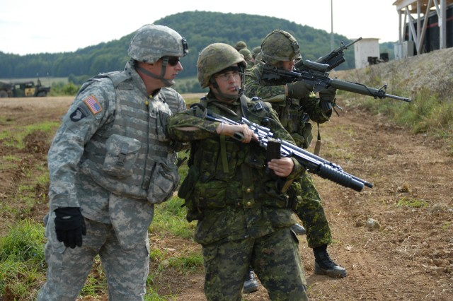 U.S. Army Sgt. 1st Class Chris Hopkins, Joint Multnational Readiness Center observer controller, checks the C-782 rifle of Canadian Army Master Cpl. Cory Matush, 4th Platoon, 2nd Battalion Royal Canadian Regiment, to make sure there is no live ammunition in the chamber after the live-fire rotation of their Military Operations on Urban Terrain training at the JMRC shoothouse Sept. 18, as part of Cooperative Spirit 2008.  Safety is a primary concern for the American, British, Canadian, Australian and New Zealand Armies' Program, which is conducting the Cooperative Spirit training event to test and close the gaps in interoperability between the nations.