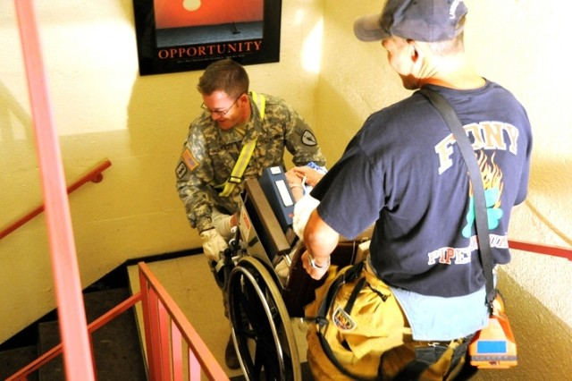Following torrential rainfall from the remnants of Hurricane Ike, the Indiana National Guard  helped evacuate people from the flooded community of Munster, Ind., Sept. 14. Staff Sgt. Travis Hackett with the 738th Medical Company of Monticello, Ind., assisted by a member of the Munster Fire Department, navigated the dark and slippery stairwells of a flooded nursing home. More than 150 patients were evacuated from the Munster Medical Inn and sent to neighboring hospitals.