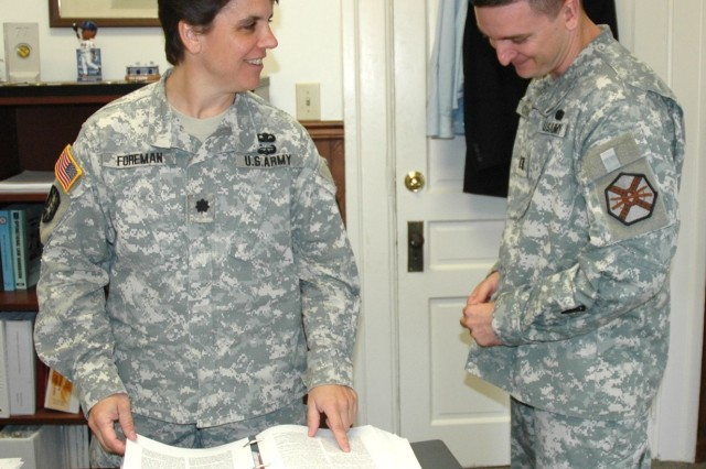 Lt. Col. Meg Foreman, Staff Judge Advocate  with U.S. Army Garrison (left), discusses legal matters with Capt. Chris Curran, an administrative law attorney assigned to ForemanAca,!a,,cs office.